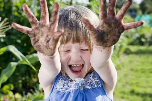 Girl(3-5) with mud hands